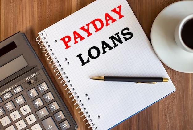 Empréstimos de pagamento escritos em um bloco de notas branco perto de uma calculadora e uma xícara de café em uma superfície de madeira escura