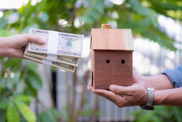 Empréstimos para a mão de conceito imobiliário segurando um dinheiro e uma casa modelo juntos no parque público