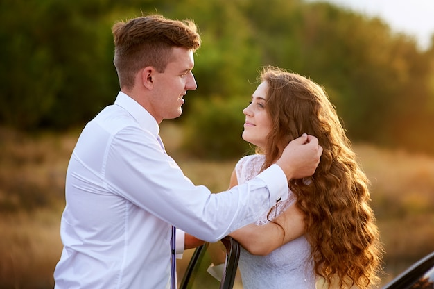 Enamoured noiva e noivo no dia do casamento ao sol do sol
