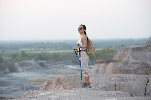 Encaixar a alpinista feminina com mochila e varas em pé no cume da montanha rochosa, olhando os vales e o pico