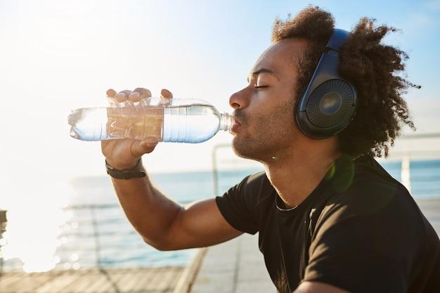 Encaixe o atleta de pele escura bebendo água de uma garrafa de plástico após um treino intenso de corrida cardiovascular.