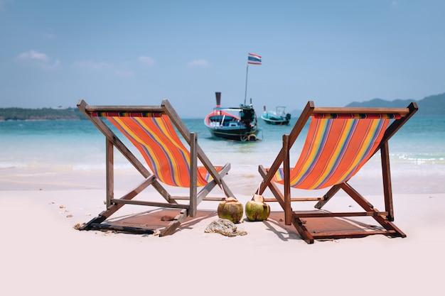 Encalhe a cena calma com espreguiçadeiras e dois coquetéis de coco perto do mar da tailândia.