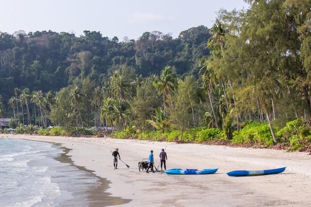 Encalhe o grupo do pessoal de limpeza no prao da área ao na ilha do koh kood, província tailândia de trat.