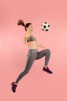 Encaminhar para a vitória. a jovem mulher como jogador de futebol, pulando e chutando a bola no estúdio sobre um fundo vermelho. fã de futebol e o conceito do campeonato mundial. conceitos de emoções humanas