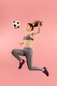 Encaminhe para a vitória. a jovem mulher como jogador de futebol, pulando e chutando a bola no estúdio sobre um fundo vermelho. fã de futebol e o conceito do campeonato mundial. conceitos de emoções humanas