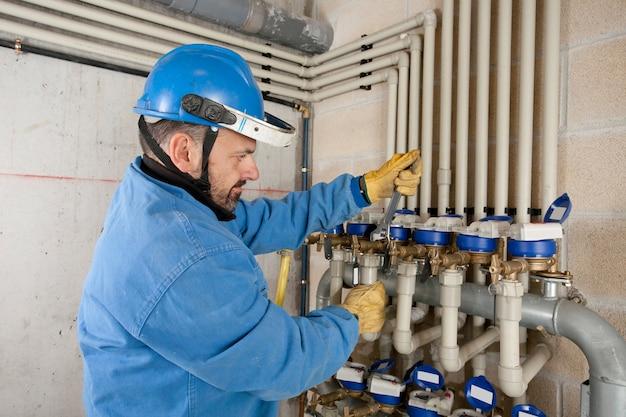 Encanador ajustando as válvulas do encanamento
