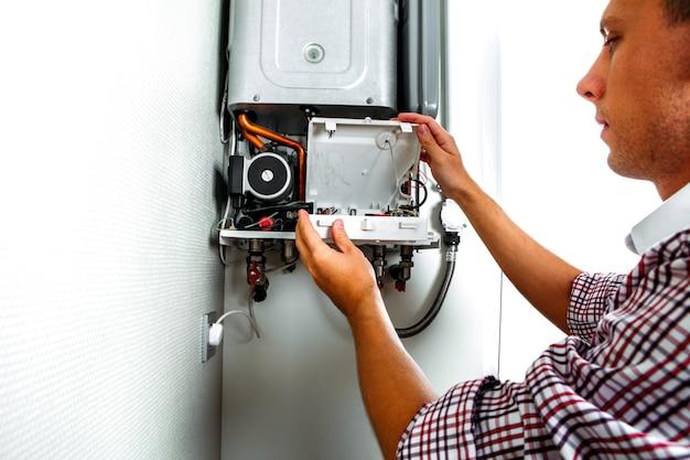 Encanador atribui tentando corrigir o problema com o equipamento de aquecimento residencial. conserto de caldeira a gás
