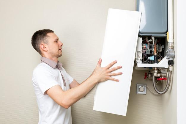 Encanador atribui tentando resolver o problema com o equipamento de aquecimento residencial. conserto de caldeira a gás