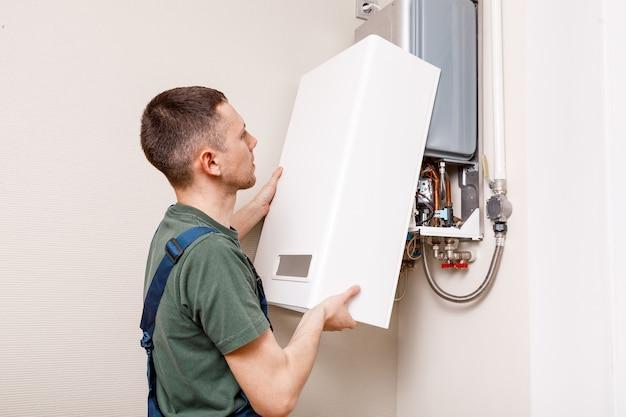 Encanador atribui tentando resolver o problema com o equipamento de aquecimento residencial. reparação de uma caldeira a gás