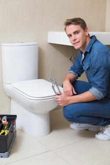 Encanador bonito com caixa de ferramentas fazendo reparação do banheiro