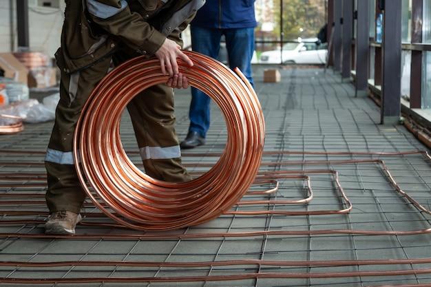 Encanador, colocando tubos de cobre no chão com aquecimento quente