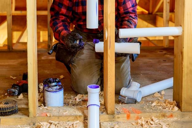 Encanador com as mãos na cola dois pedaços de tubo de pvc de drenos de plástico, close-up no novo banheiro