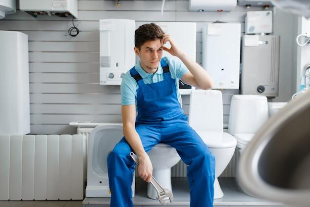 Encanador com chaves de cachimbo sentado no vaso sanitário na vitrine da loja de encanamento. homem comprando ferramentas e equipamentos de engenharia sanitária na loja
