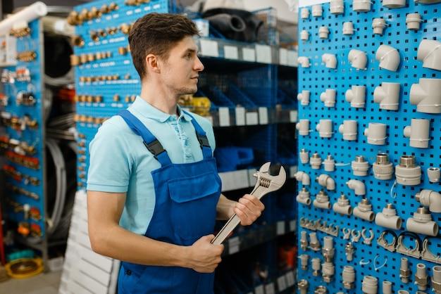 Encanador com chaves de cano posa na vitrine, escolha da loja de encanamento. homem comprando ferramentas e equipamentos de engenharia sanitária na loja