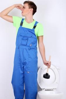 Encanador com desentupidor de vaso sanitário aceso