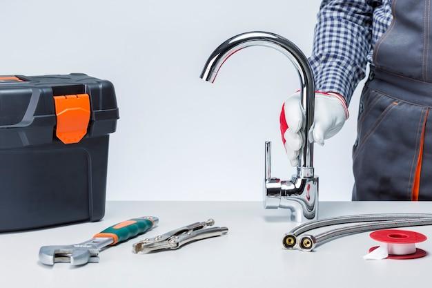 Encanador com torneira e caixa de ferramentas com ferramentas