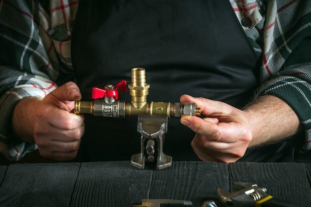 Encanador conecta acessórios de latão enquanto repara o equipamento close-up das mãos do mestre durante o trabalho