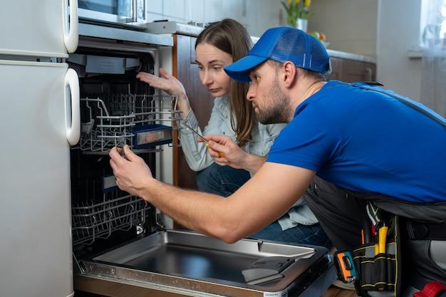 Encanador conserta a máquina de lavar louça e fala com a dona de casa