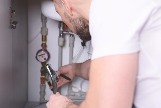 Encanador consertando canos de pia na cozinha, close-up
