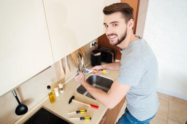 Encanador consertando torneira de água com chave inglesa