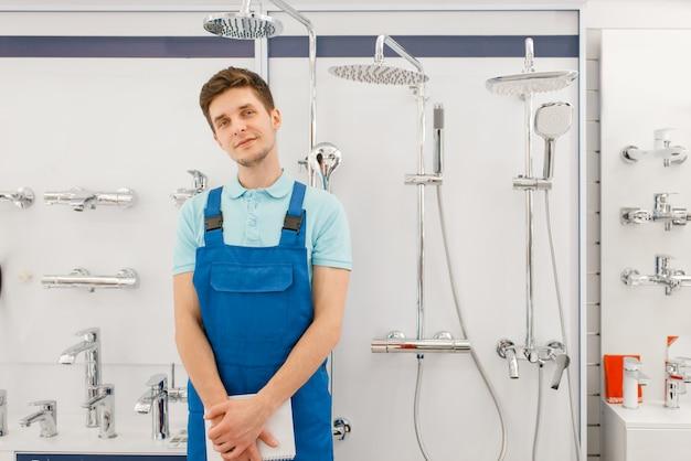 Encanador de uniforme na vitrine com caldeiras na loja de encanamento. homem com notebook comprando engenharia sanitária na loja, escolha de torneiras e torneiras