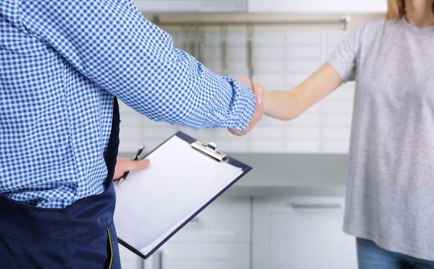 Encanador e mulher apertando as mãos em casa