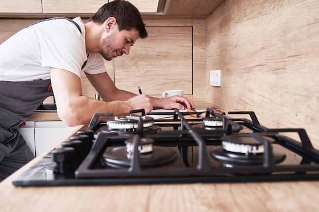 Encanador fardado assina contrato de prestação de serviços na cozinha