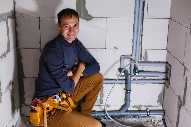 Encanador faz fiação de canos de esgoto