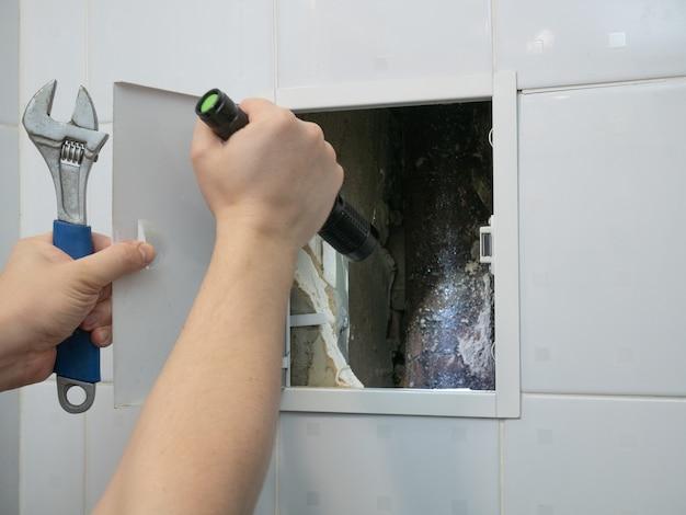Encanador faz-tudo inspecionando tubulações no banheiro com lanterna