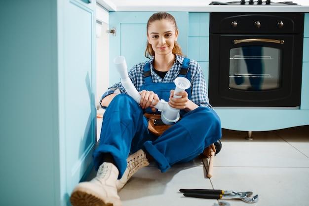 Encanador feminino bonito de uniforme detém o tubo de drenagem na cozinha. handywoman com pia de conserto de bolsa de ferramentas, serviço de equipamento sanitário em casa