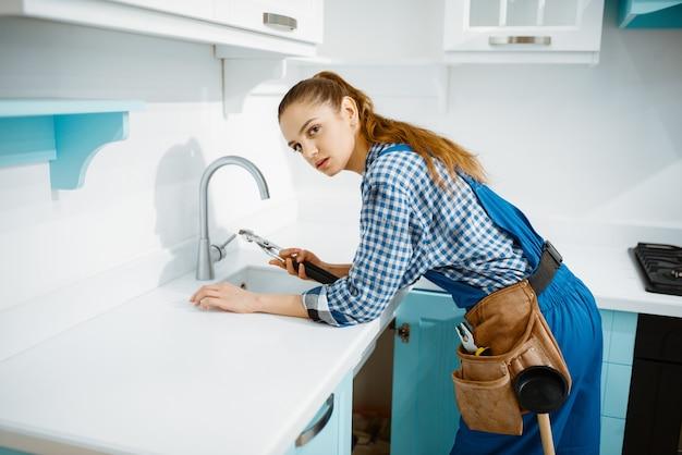 Encanador feminino bonito na torneira de fixação de uniforme na cozinha. handywoman com pia de conserto de bolsa de ferramentas, serviço de equipamento sanitário em casa