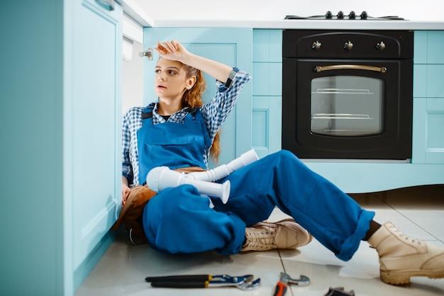 Encanador feminino cansado de uniforme, instalando o tubo de drenagem na cozinha. handywoman com pia de conserto de bolsa de ferramentas, serviço de equipamento sanitário em casa
