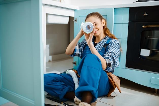 Encanador feminino de uniforme deitado no chão da cozinha, vista superior. handywoman com pia de conserto de bolsa de ferramentas, serviço de equipamento sanitário em casa