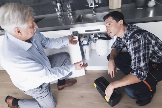Encanador homem fala com um cliente que está insatisfeito.
