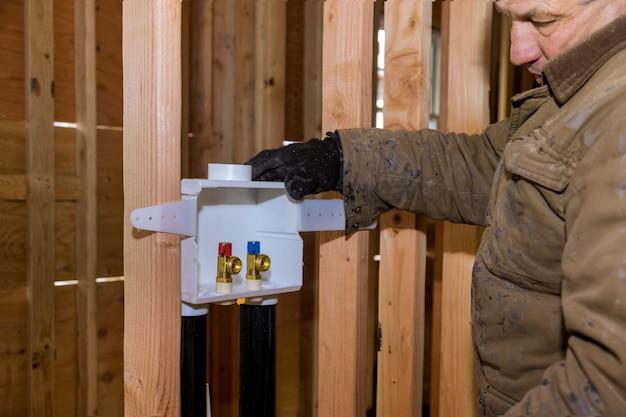 Encanador instalando caixas de saída de lavanderia com nova máquina de lavar de suprimentos para casa
