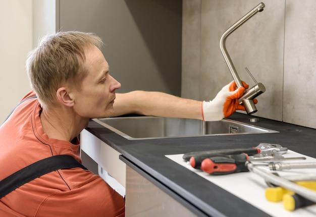 Encanador instalando uma torneira na pia da cozinha