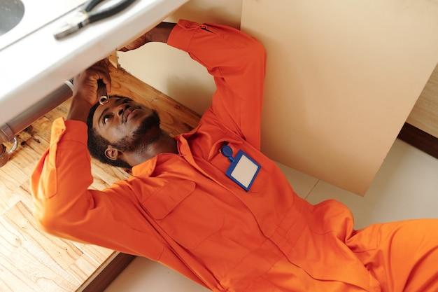 Encanador jovem concentrado de barba negra com distintivo no peito deitado embaixo da pia e consertando ralos entupidos