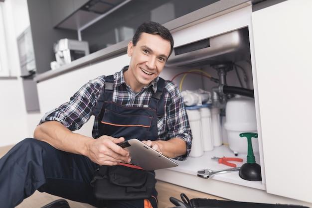 Encanador jovem está sentado perto da pia com um tablet.