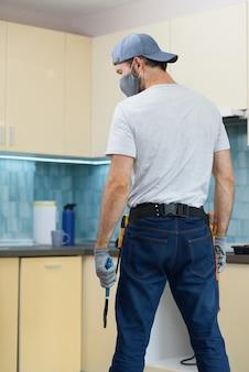Encanador jovem reparador usando uma máscara segurando uma chave inglesa enquanto se prepara para consertar uma pia