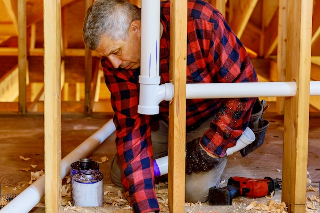 Encanador juntando tubos de plástico com cola para ralos em uma construção nova casa