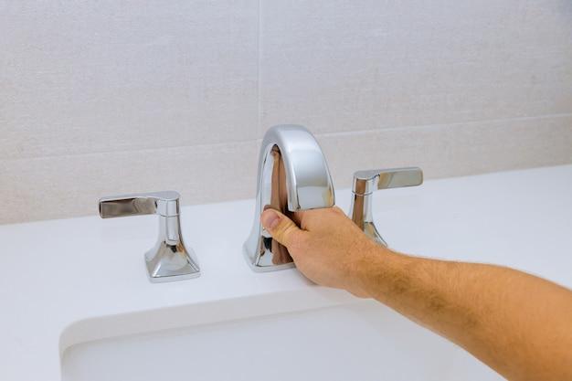 Encanador masculino consertando a torneira de uma pia no banheiro
