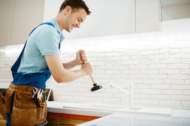 Encanador masculino de uniforme detém o êmbolo, problema com entupimento na cozinha. faz-tudo com pia de conserto de bolsa de ferramentas, serviço de equipamento sanitário em casa