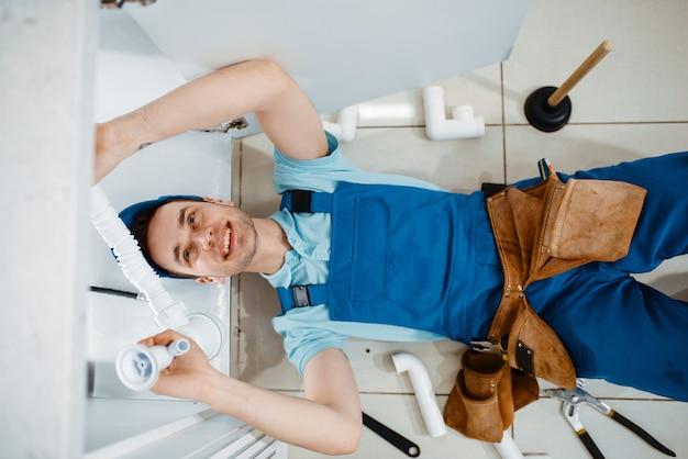 Encanador masculino de uniforme, instalando o tubo de drenagem na cozinha, vista superior. handywoman com pia de conserto de bolsa de ferramentas, serviço de equipamento sanitário em casa