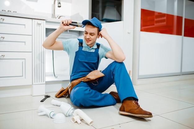 Encanador masculino de uniforme sorridente segurando tubo de drenagem