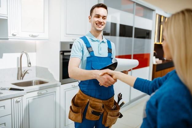 Encanador masculino e cliente feminino na cozinha