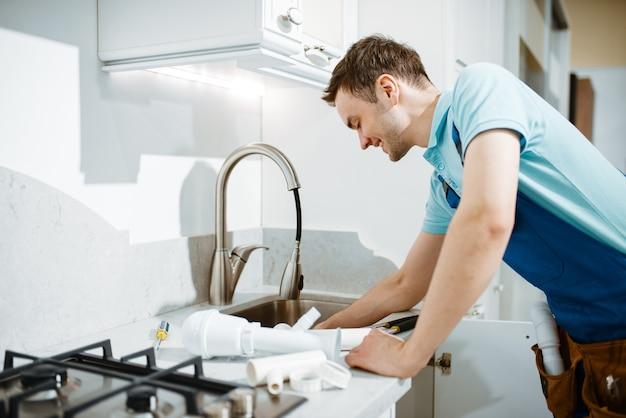Encanador masculino em uniforme, consertando o problema com torneira na cozinha. faz-tudo com pia de conserto de bolsa de ferramentas, serviço de equipamento sanitário em casa