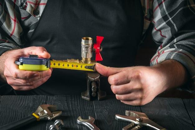 Encanador mestre mede a distância usando fita métrica ambiente de trabalho na oficina com ferramentas
