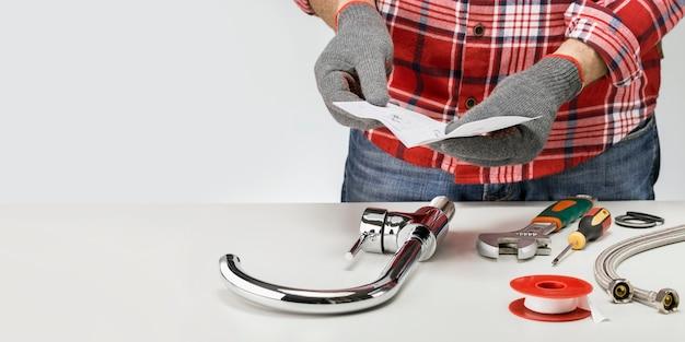 Encanador, montagem da torneira da cozinha. homem e torneira com ferramentas na superfície cinza com espaço de cópia.