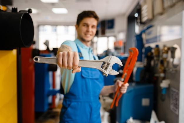 Encanador mostra chaves de tubos em loja de encanamento