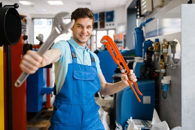 Encanador mostra chaves de tubos na vitrine da loja de encanadores.